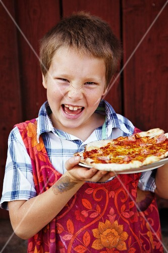 Boy holding pizza, laughing