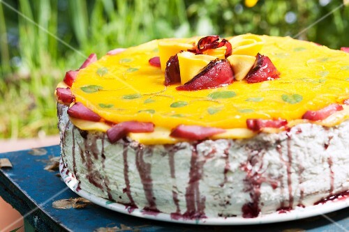 A colourful cream layer cake for a birthday, with assorted fruits