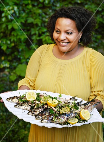 Woman carrying tray of grilled fish