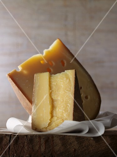 Two wedges of hard cheese on paper