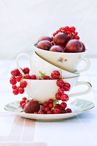 Redcurrants and red gooseberries in a stack of old cups