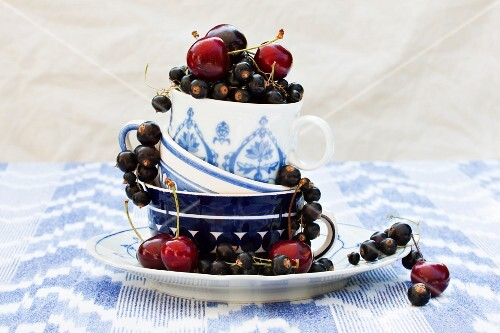 Blackcurrants and cherries in stacked teacups