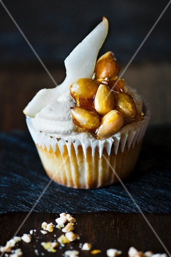 Single cupcake with slice of pear and sugar almonds