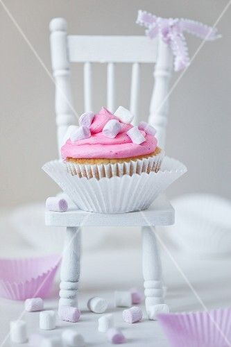 Single marsmallow cupcake with white and pink marshmallows, cupcake cases on a white dolls house chair