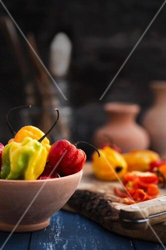 Assorted Habanero chillies in a bowl and on a chopping board