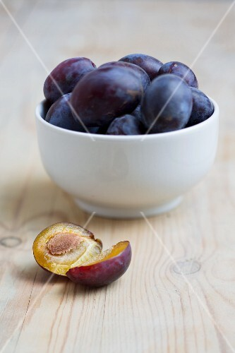 Plums in a bowl, with a halved plum in front of the bowl