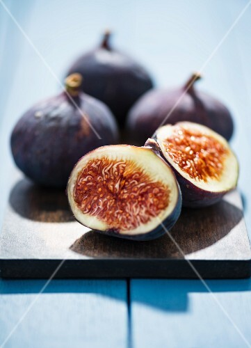 Fresh red figs on a chopping board, one cut in half