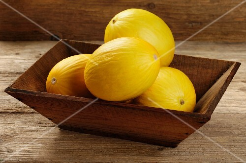 Several honeydew melons in a wooden bowl