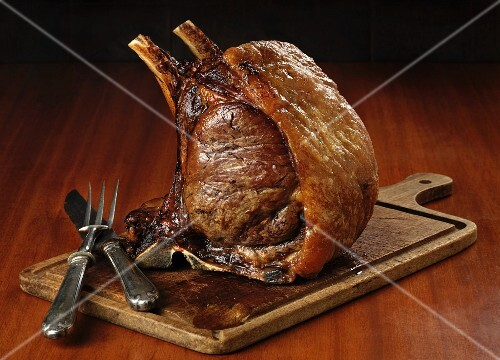 Roast rack of beef on a chopping board