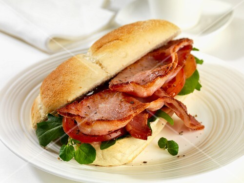 A bread roll filled with bacon, tomatoes, rocket and watercress
