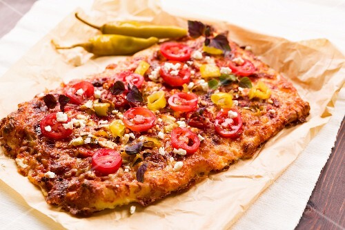 Pizza topped with hot peppers, feta and fresh tomatoes