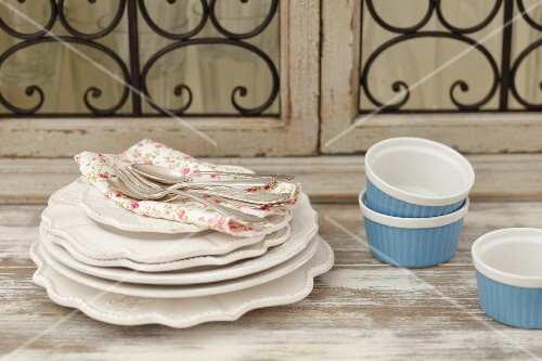 A stack of plates, a floral cloth, cutlery and ramekins