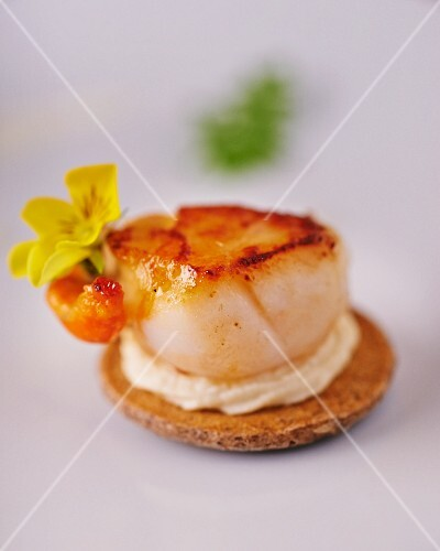 A pancake topped with a fried scallop