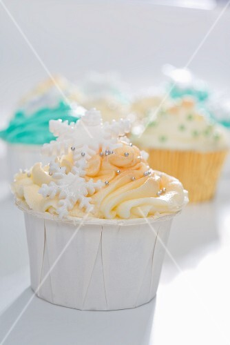 A cupcake decorated with yellow icing, silver balls and snowflakes