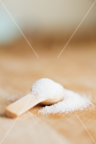Granulated sugar on a wooden spoon