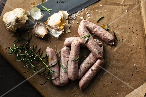 Sausages, garlic and rosemary on grease-proof paper