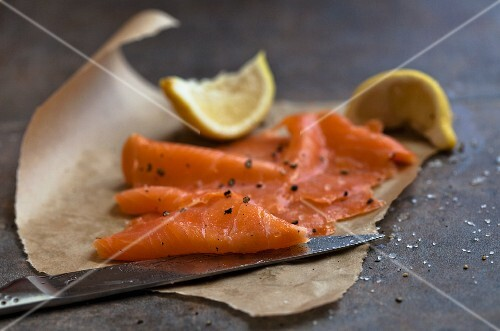 Smoked salmon, lemon wedges and a knife, on grease-proof paper