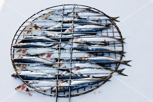 Raw sardines in a barbecue basket