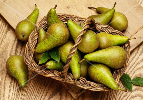 Fresh Conference pears with leaves in a basket