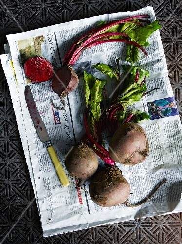 Several beetroot on newspaper