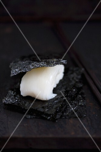 Nigiri sushi with squid (tai) between pieces of salty nori (Japan)