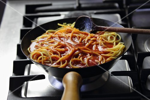 Spaghetti with tomato sauce in a pan on a gas hob