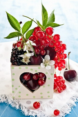 Assorted berries in a wooden box with a heart