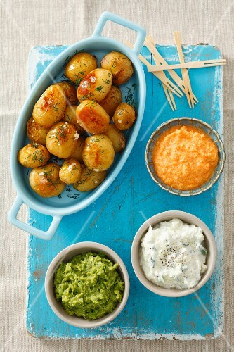 Baked potatoes with three dips (pea dip, carrot dip, tzatziki)