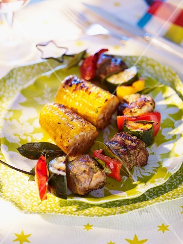 Barbecued lamb skewer with corn on the cob
