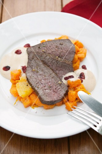 Roasted leg of venison with cranberry hollandaise and sweet potatoes cooked with orange