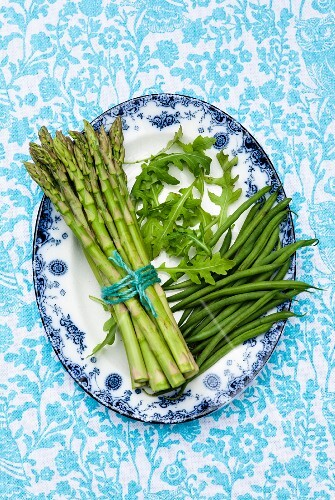 Green asparagus, rocket and beans on a patterned plate