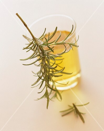 A small glass of oil with a sprig of rosemary