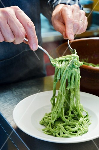 A man serving green tagliatelle