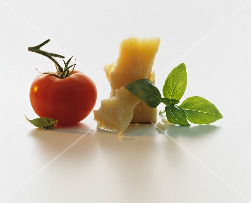 A still life featuring a tomato, parmesan and basil