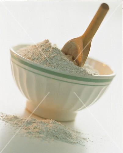 A bowl of flour and a wooden spoon