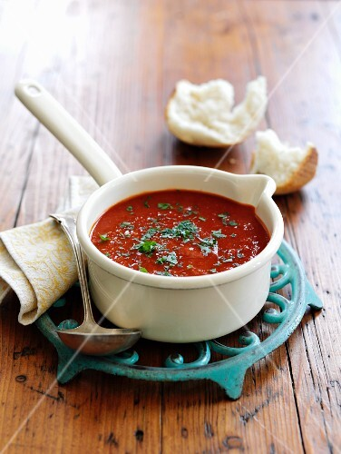 Tomato soup with fresh herbs in a saucepan