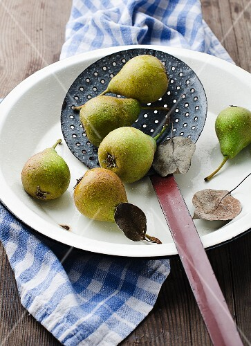 Several pears with water drops in a dish with a slotted spoon