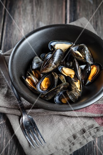 Steamed mussels in a black dish on a linen cloth