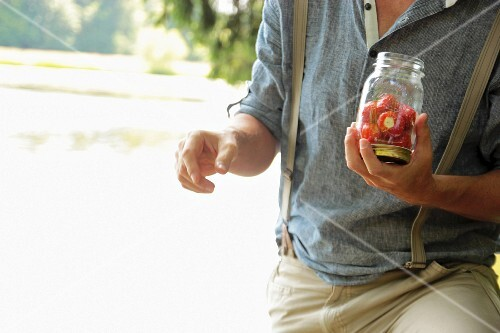 A man holding a glass of stuffed cherry peppers next to a lake