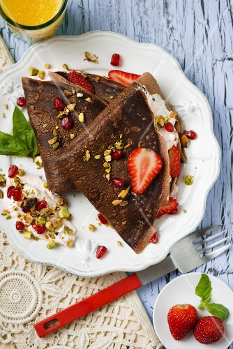 Chocolate pancake with cream, strawberries and pistachios