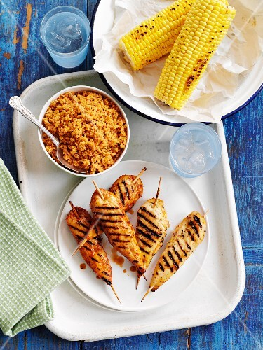 Grilled chicken skewers with couscous and corn on the cob