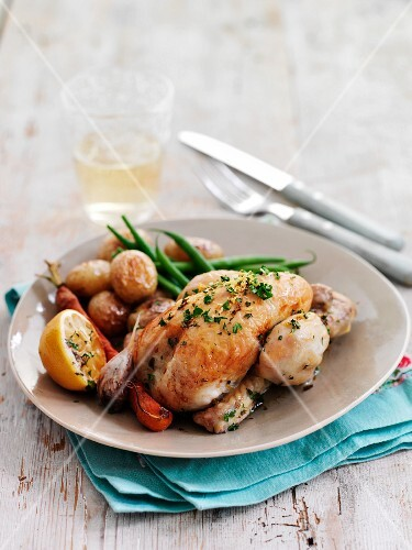 Roast spring chickens with lemons, potatoes and sliced peppers