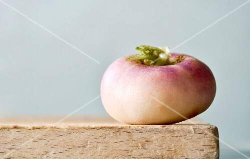 An individual white turnip on a wooden board
