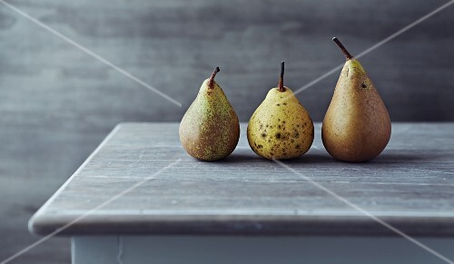 still life with three autumn pears on an old table