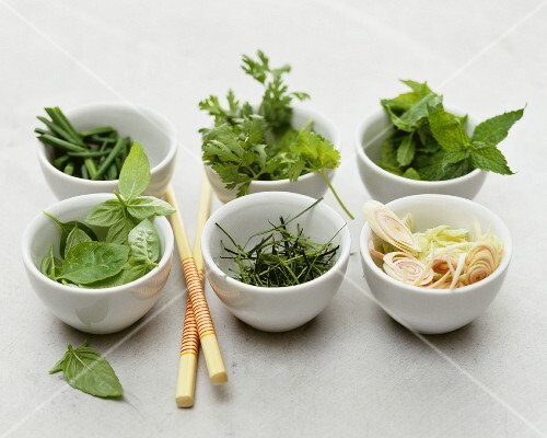 Assorted fresh herbs in small porcelain bowls