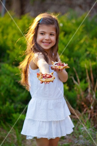 Little girl holding rhubarb tartlets in a garden