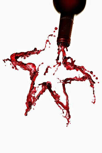 A star made from red wine, against a white background