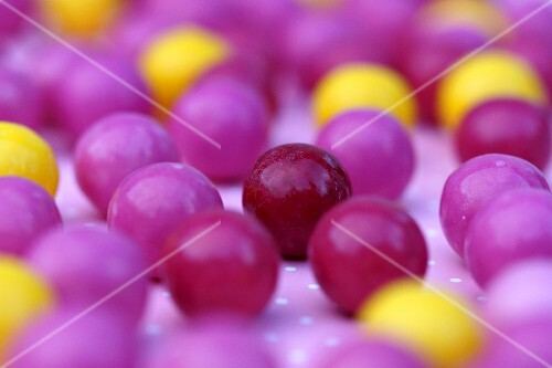 Lots of pink and yellow gumballs (close up)