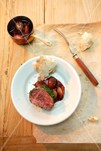 Beef fillet with a herb crust cooked in dough; served with shallots cooked in red wine