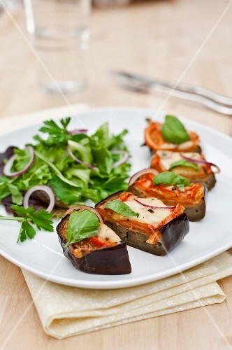Aubergines with tomatoes and mozzarella cooked in the oven; served with a green salad